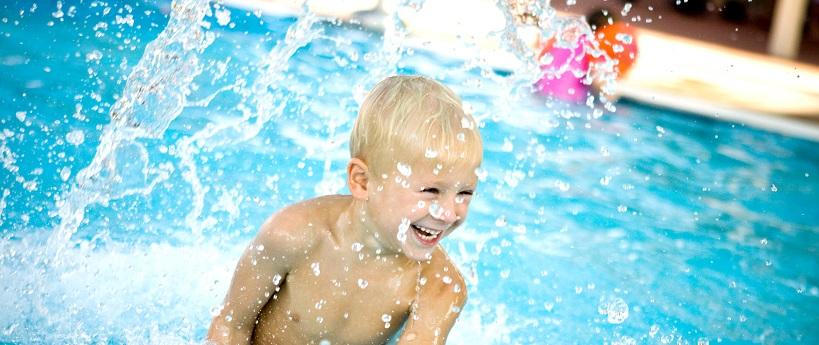Smiling boy splashing in a pool